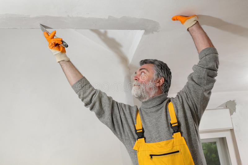 Worker repairing plaster at ceiling. Worker spreading plaster to wall, corner protecting batten install, repairing works royalty free stock images