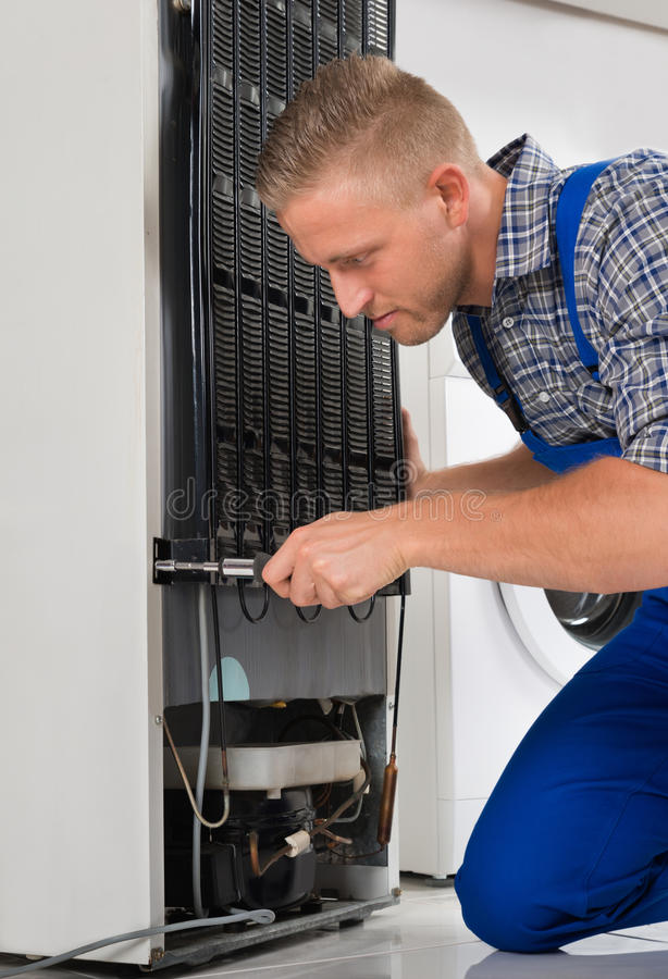 Worker Repairing Refrigerator In House royalty free stock photos