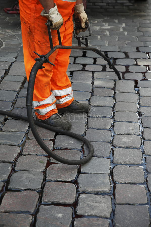 Worker repairing stone road. Closeup view of a street worker repairing a stone road with liquid sealant being applied between the stones royalty free stock image