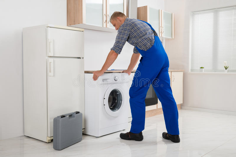 Worker Repairing Washer royalty free stock images