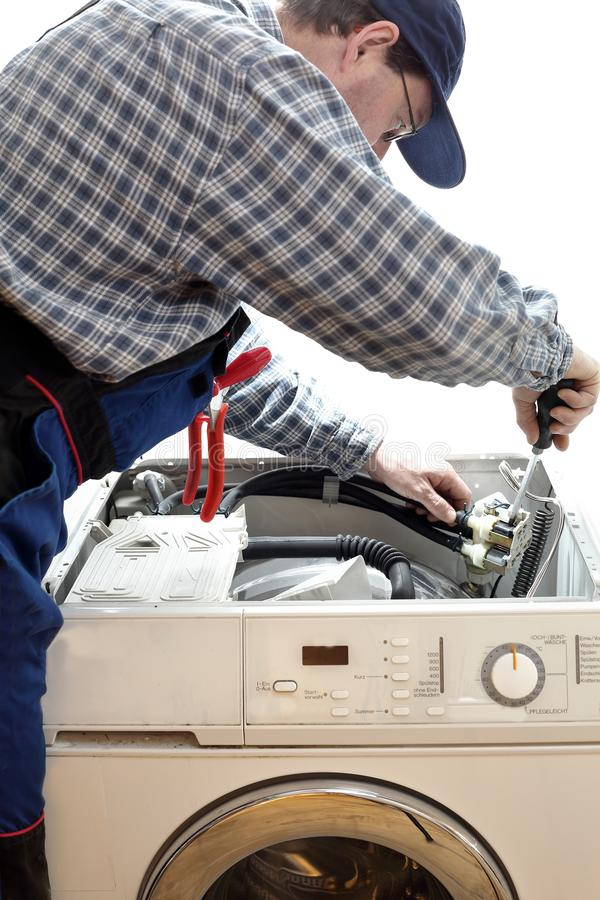 Worker is repairing a washing machine. With tools stock photos