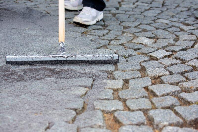 Worker resurfacing cobblestones royalty free stock photos