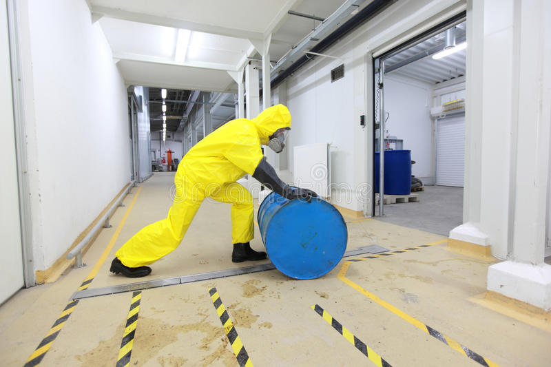 Worker rolling the barrel with toxic substance. Fully protected in yellow uniform,mask,and rubber gloves and boots worker,rolling the barrel with toxic substance stock photography