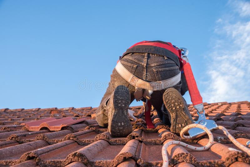 Worker at the rooftop with security gear. Worker at the rooftop, with security equipment, replacing old roof tiles. blue sky with copy space stock photo