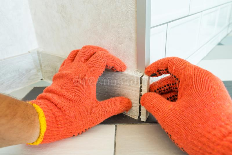 Worker`s hands Instal plastic skirting board and decorative caps. Renovation of baseboard at home. royalty free stock images