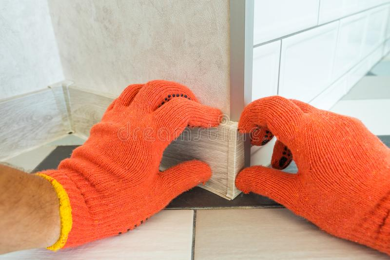 Worker`s hands Instal plastic skirting board and decorative caps. Renovation of baseboard at home. stock photos