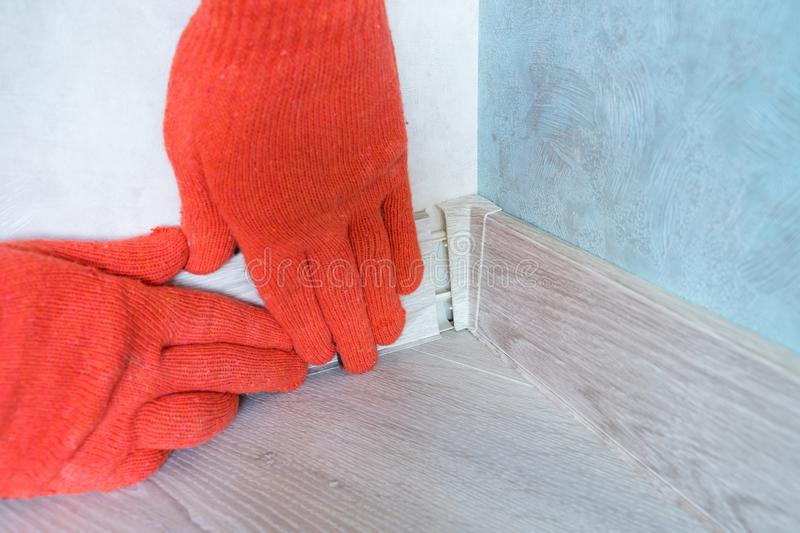 Worker`s hands Instal plastic skirting board and decorative caps. Renovation of baseboard at home. Worker`s hands Instal plastic skirting board on laminate royalty free stock photo