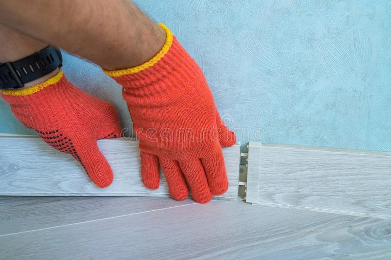 Worker`s hands Instal plastic skirting board on laminate flooring. Renovation of baseboard at home. royalty free stock photo
