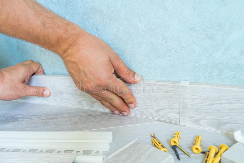 Worker`s hands Instal plastic skirting board on laminate flooring. Renovation of baseboard at home stock images