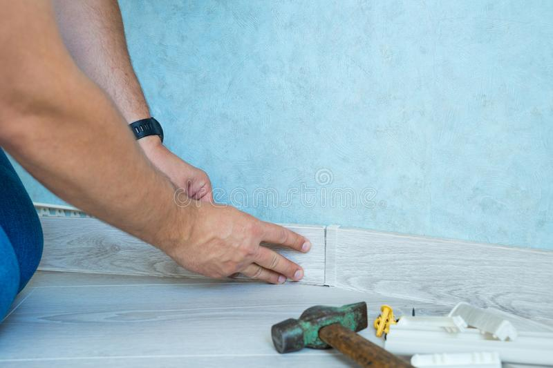 Worker`s hands Instal plastic skirting board on laminate flooring. Renovation of baseboard at home. Worker`s hands Instal plastic skirting board on laminate stock photo