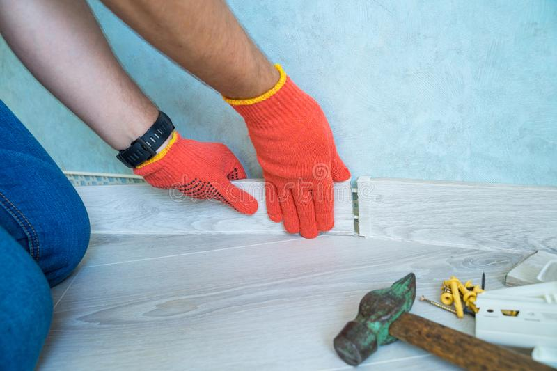 Worker`s hands Instal plastic skirting board on laminate flooring. Renovation of baseboard at home. Worker`s hands Instal plastic skirting board on laminate royalty free stock photo