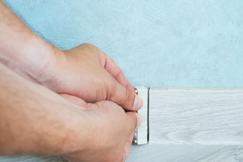 Worker`s hands Instal plastic skirting board on laminate flooring. Renovation of baseboard at home royalty free stock images