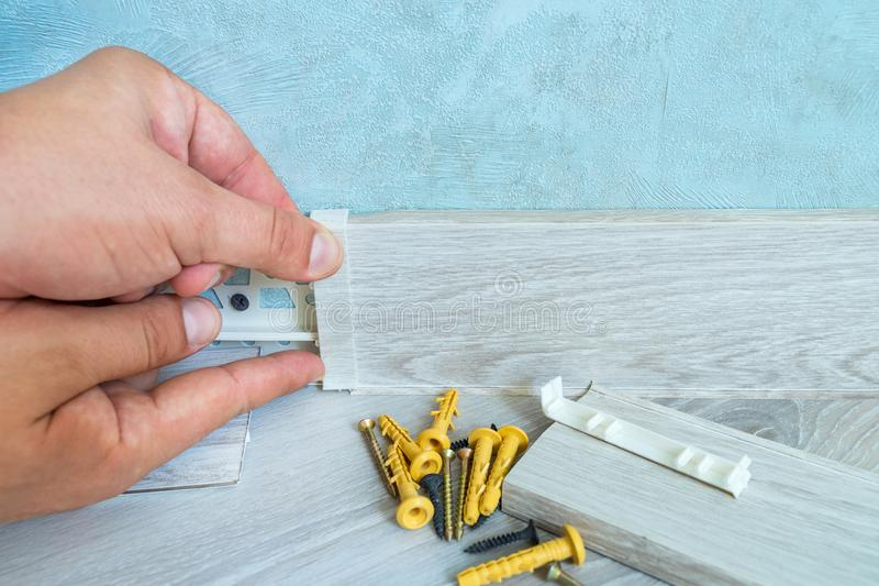 Worker`s hands Instal plastic skirting board on laminate flooring. Renovation of baseboard at home. stock image