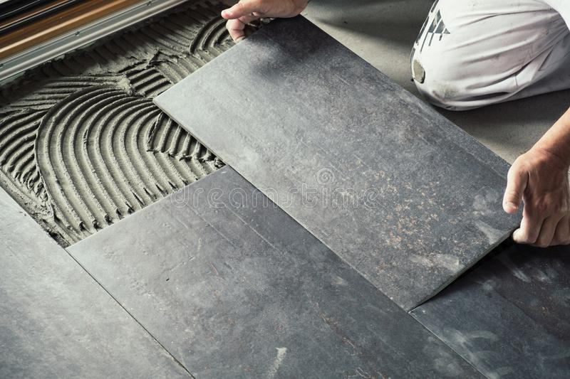 Worker placing ceramic floor tiles on adhesive surface. Worker`s hands placing ceramic floor tile with precision on adhesive surface stock image