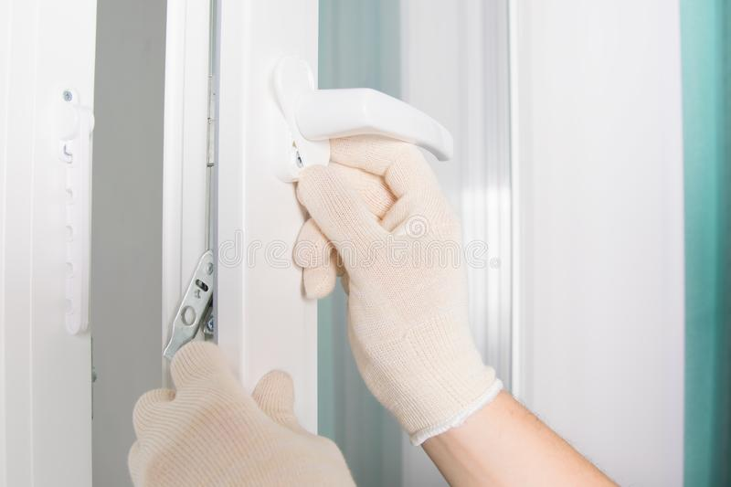 Worker's hands in protective gloves, close the cover of the plastic window handle fastening, close-up stock photo
