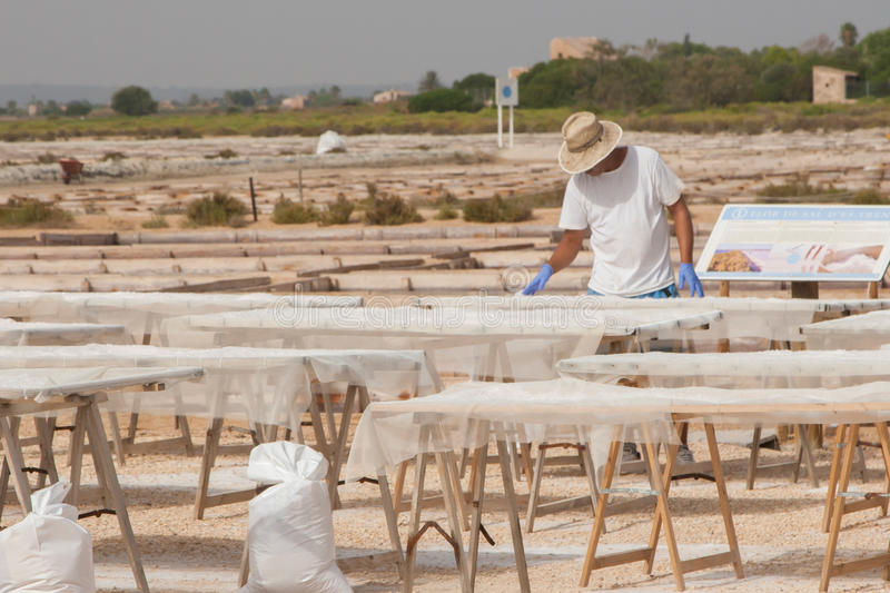 Worker on saltern. On Mallorca island is sorting and packaging salt for sale