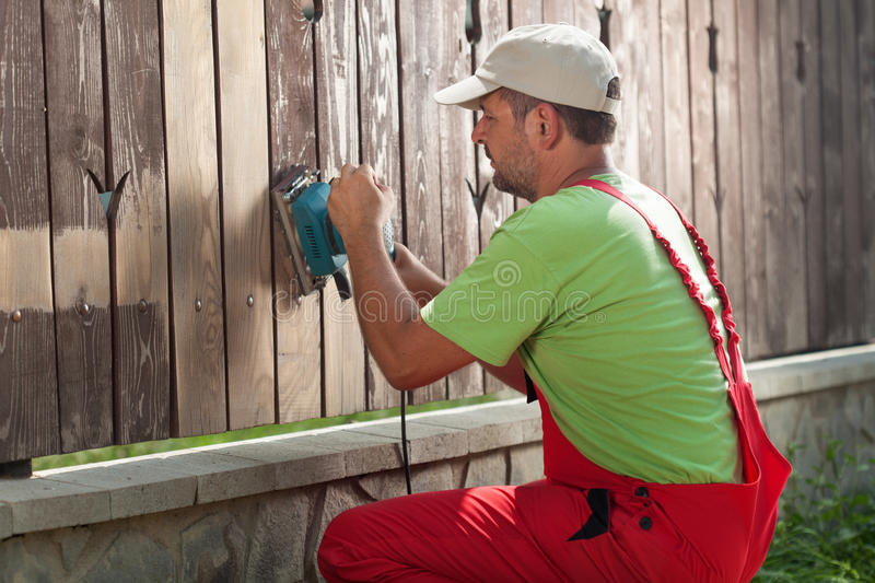 Worker sanding away old paint from a wooden fence royalty free stock photos