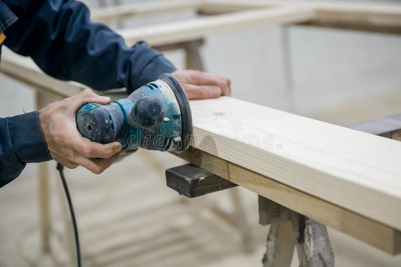 Worker sanding the wooden surface. In the hand of the power tool stock photography