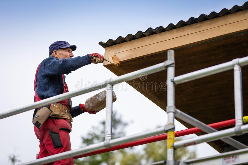 Man on scaffolding painting house roof planks with paint roller royalty free stock photography