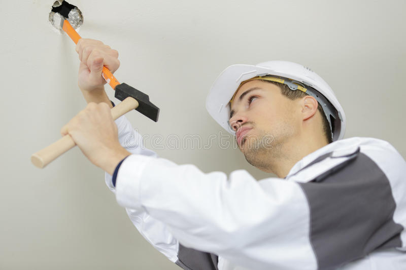 Worker scrapes old paint on ceiling stock photos