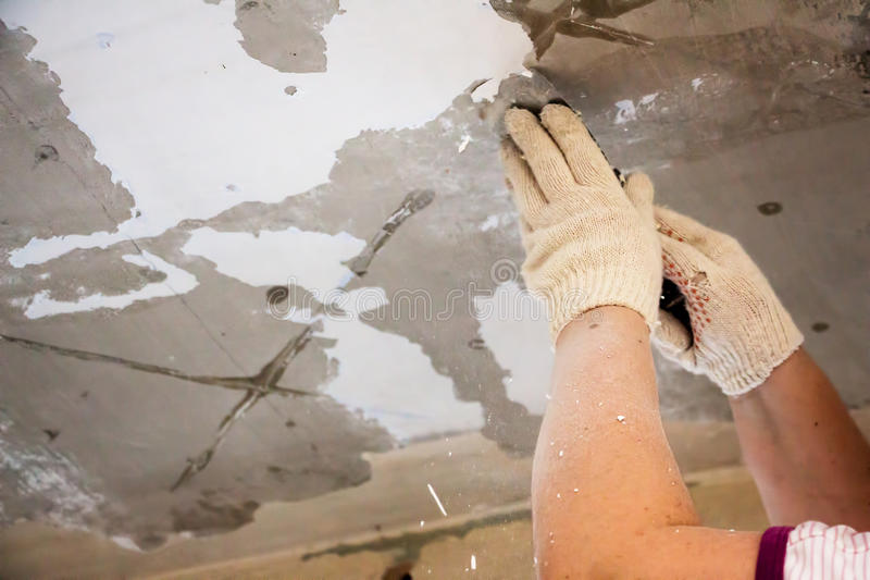 Worker scrapes the old paint stock photos