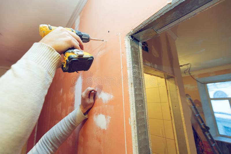 Worker is screwing the drywall by gun to the plasteboard wall in apartment is inder construction, remodeling. Renovation, overhaul, extension, restoration and royalty free stock image