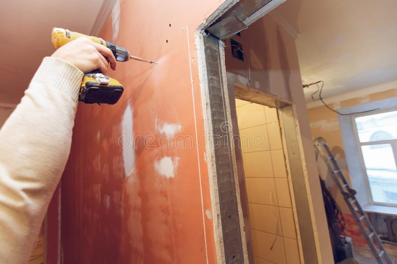 Worker is screwing the drywall by gun to the plasteboard wall in apartment is inder construction, remodeling. Renovation, overhaul, extension, restoration and royalty free stock images