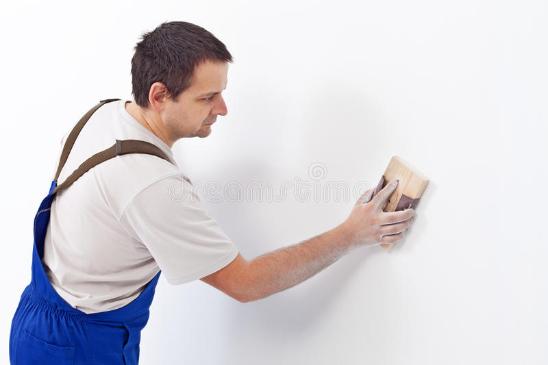 Worker scrubbing the wall with sandpaper royalty free stock image
