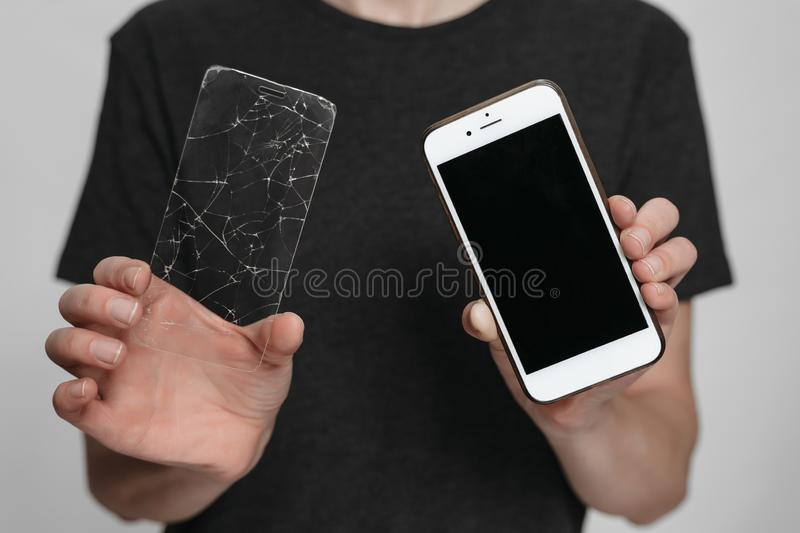 Worker of service center holding in hands smartphone and broken screen protection. Phone save concept. Isolated on gray background royalty free stock images