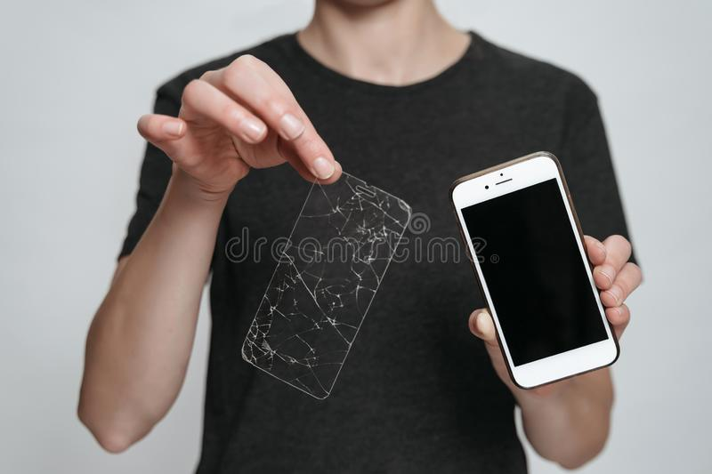 Worker of service center showing smartphone and broken screen protection. Phone repair concept. Isolated on gray background stock photo