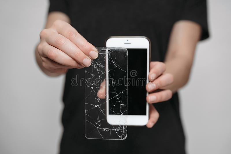 Worker of service center showing smartphone while using protection screen. Phone save concept. Isolated on gray background stock images