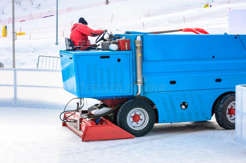 A worker is shooting a special ice maintenant machine at a sports rink. Cooking place for skating. ice preparation at the rink stock photos