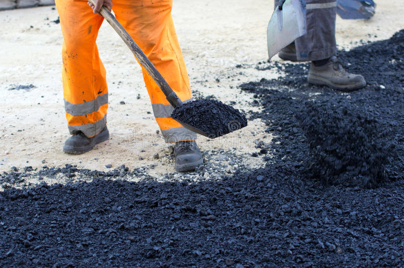Worker with shovel on asphalt royalty free stock images