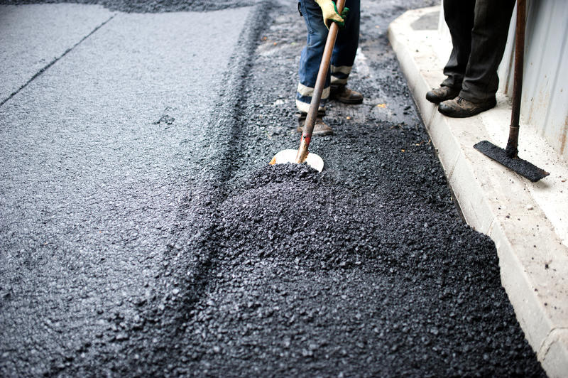 Worker with shovel doing manual labor at road construction stock image