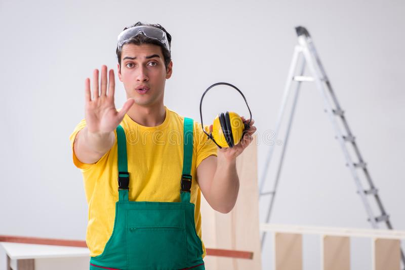 Worker showing the importnace of wearing noise cancelling headph stock photography