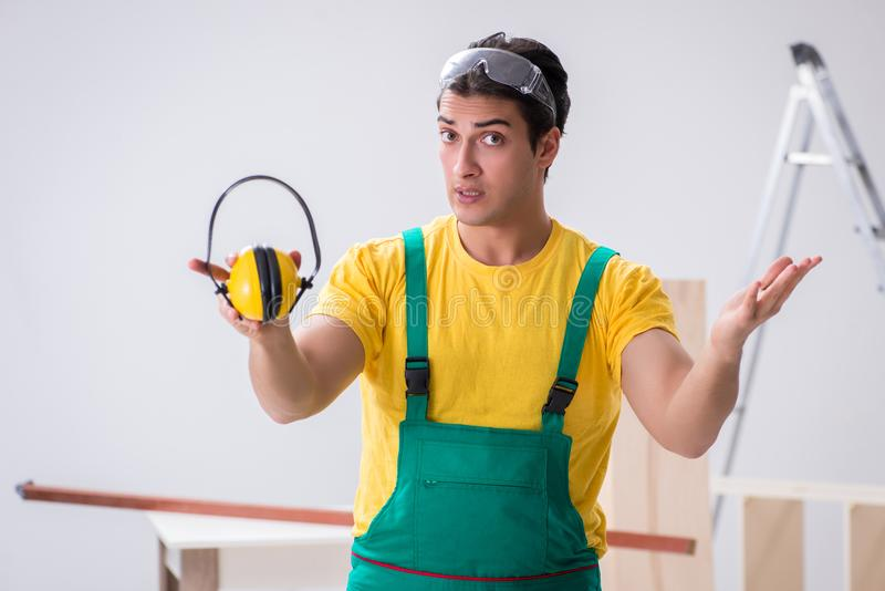 Worker showing the importnace of wearing noise cancelling headph. Ones stock photos