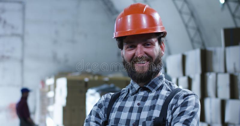 Worker smiling into camera in a warehouse. Medium close up shot of worker smiling into camera in a warehouse stock images
