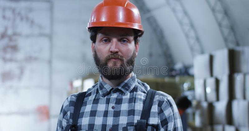 Worker smiling into camera in a warehouse. Medium close up shot of worker smiling into camera in a warehouse royalty free stock image