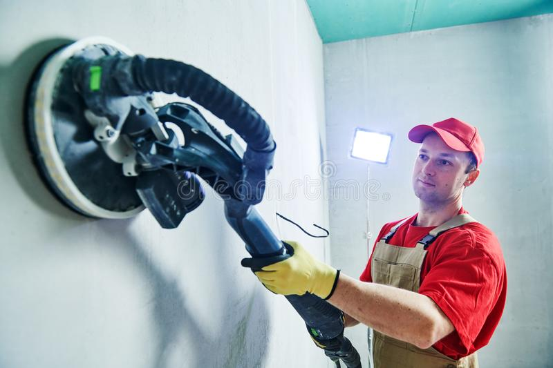 Worker smoothig and finishing wall with long reach sander before painting stock photos