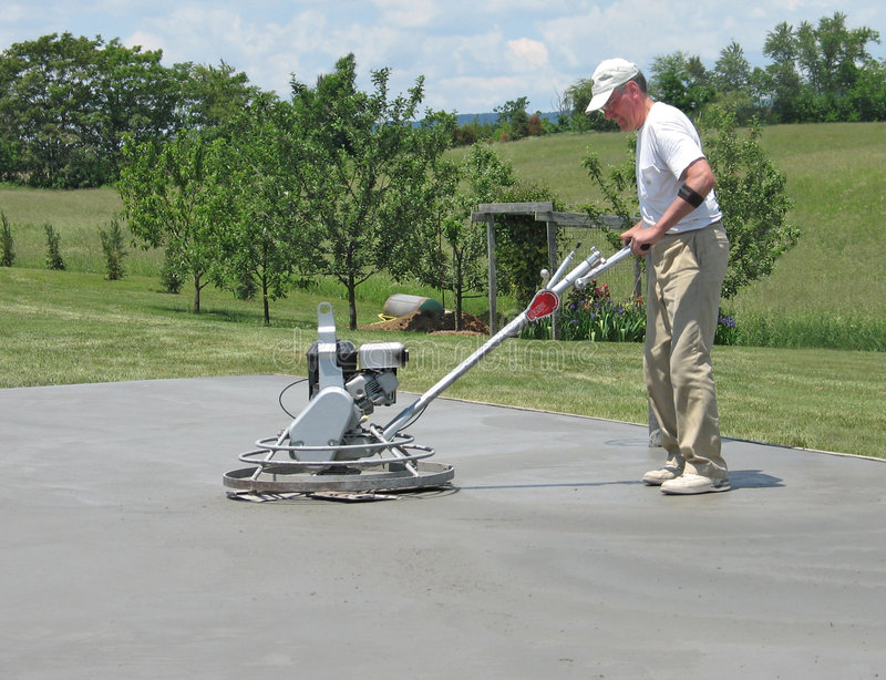 Worker smoothing concrete with a power trowel. Worker smoothing a concrete slab with a power trowel royalty free stock images