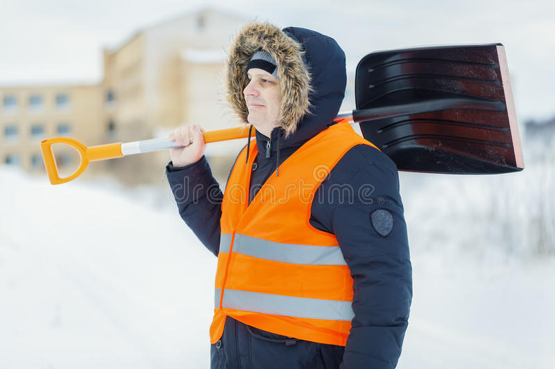 Worker with snow shovel near building in winter royalty free stock photo