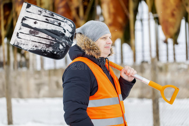 Worker with snow shovel near tanks in winter stock image