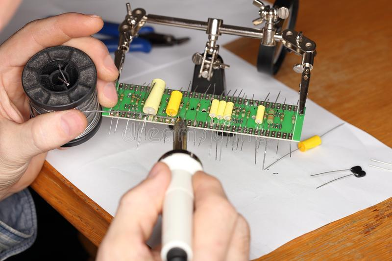 Worker is soldering some electronic elements. On a board royalty free stock image