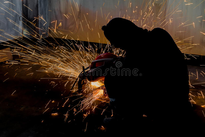 Worker and sparks of bonfire while grinding iron royalty free stock photography