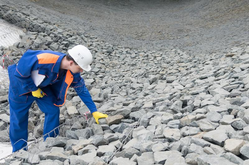 A worker in special clothing checks the quality of stones at a construction site royalty free stock photos