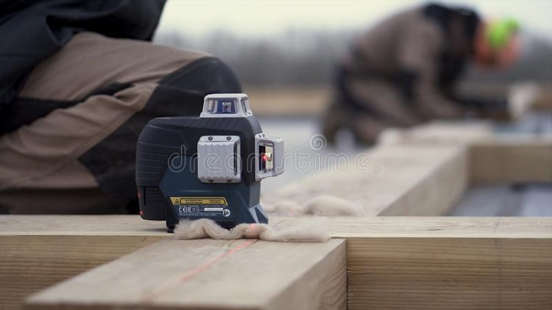 A worker in special protective uniform leveling a wooden beam while building a house foundation. Clip. Close up for a stock images