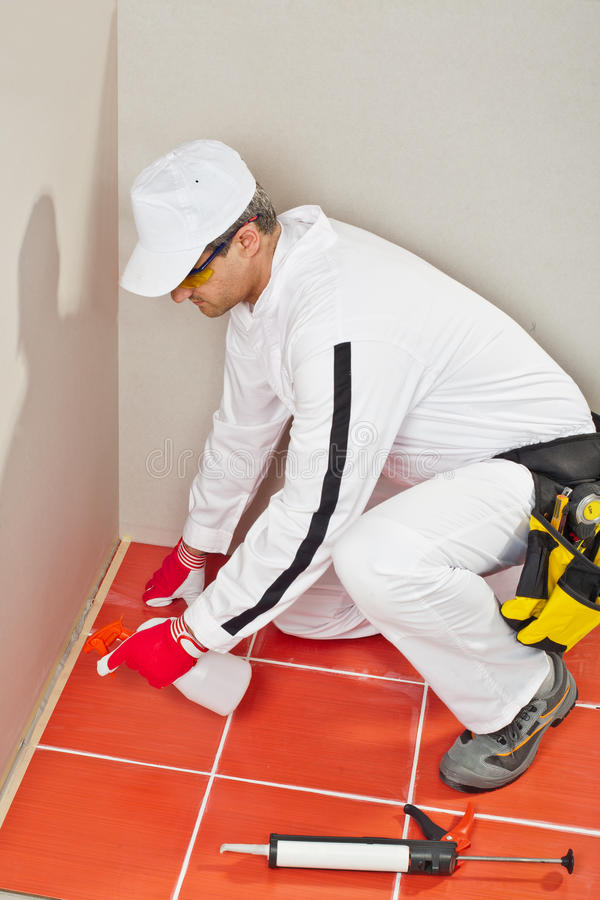 Worker sprayed silicone sealant stock image