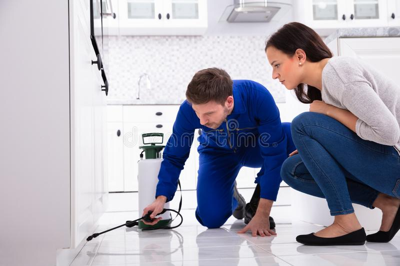Worker Spraying Insecticide Chemical At Kitchen. Male Worker Spraying Insecticide Chemical In Front Of Housewife In Kitchen stock photography
