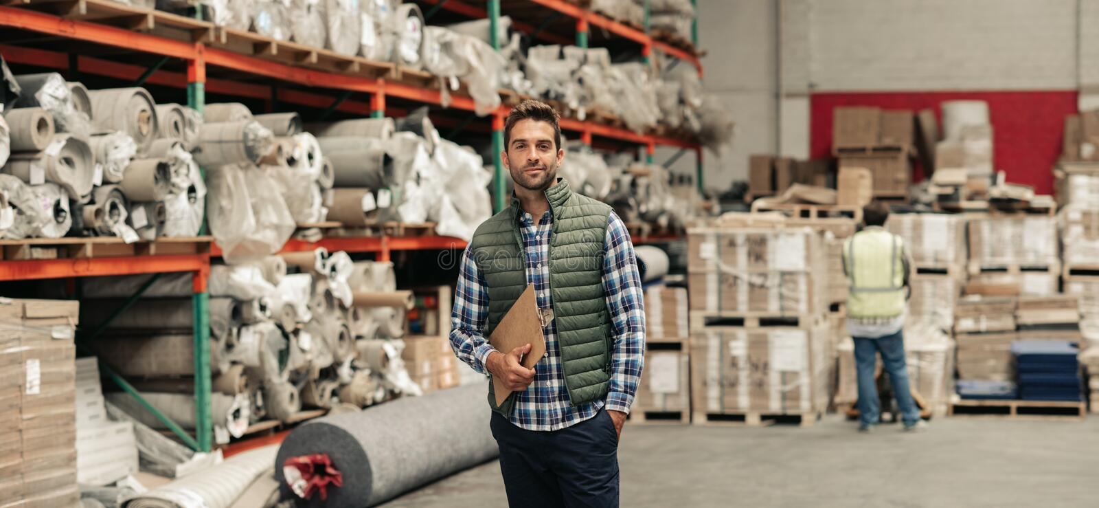 Worker standing with an inventory clipboard on a warehouse floor royalty free stock image