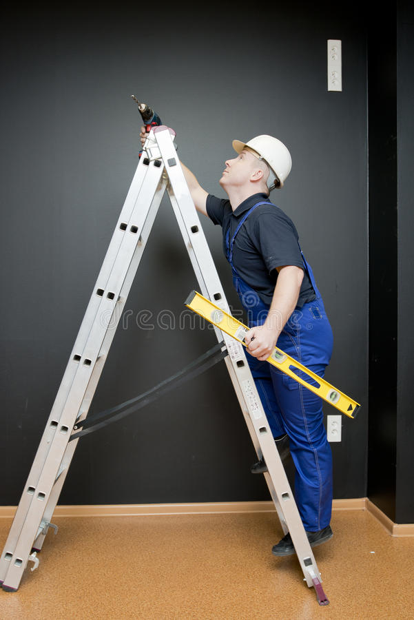 Worker standing on a ladder stock photography